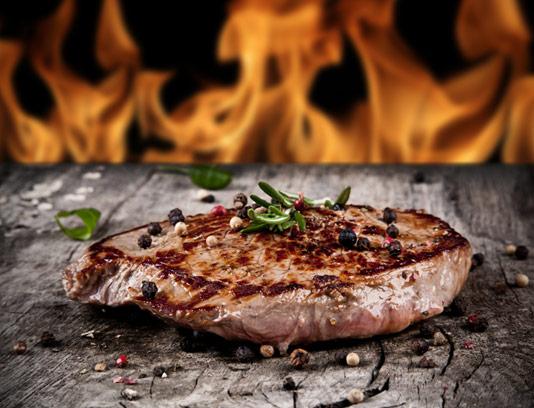 عکس با کیفیت استیک گوشت با زمینه چوبی و شعله آتش