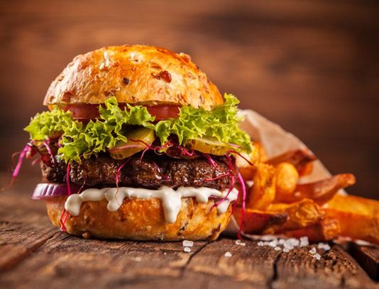 همبرگر ویژه با سس مایونز روی میز چوبی