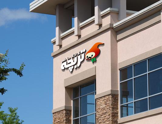 موکاپ لوگوی رستوران لایه باز در نمای سنگی ساختمان