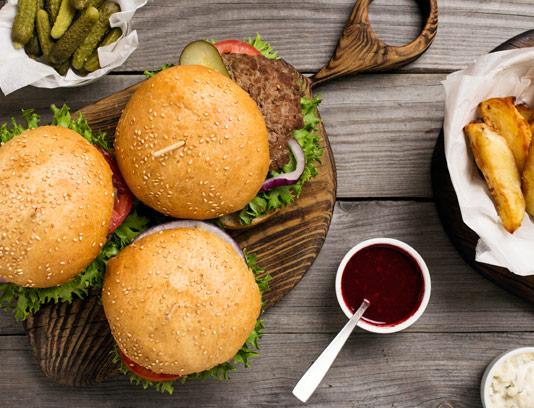 عکس با کیفیت سه ساندویچ همبرگر با سس کچاپ و سیب زمینی سرخ شده