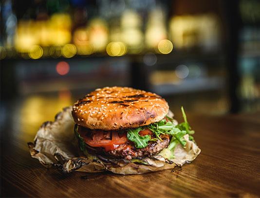 عکس با کیفیت همبرگر تنوری روی میز چوبی
