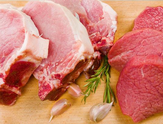 عکس با کیفیت گوشت قرمز تازه با سیر بر روی میز چوبی