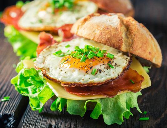 عکس با کیفیت ساندویچ تخم مرغ سرخ شده با بیکن و پنیر چدار