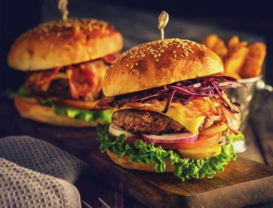 عکس با کیفیت همبرگر ویژه با بشقاب چوبی