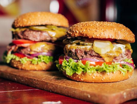 عکس با کیفیت دو ساندویچ همبرگر ویژه با بشقاب چوبی