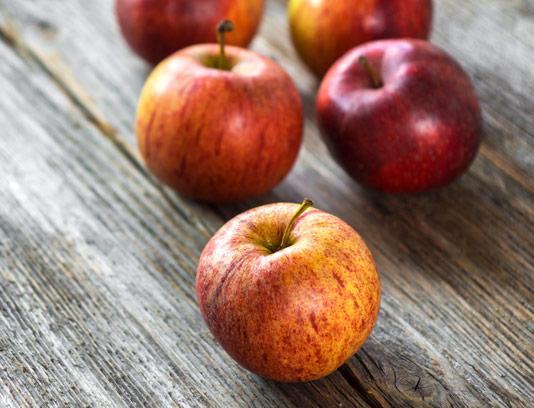 عکس با کیفیت سیب قرمز با بکگراند چوبی