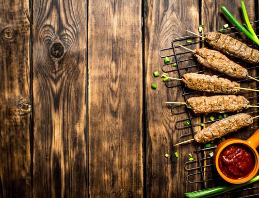 عکس با کیفیت کباب ماهیتابه ای با میز چوبی