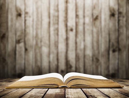 عکس با کیفیت کتاب قدیمی باز شده با بکگراند چوبی