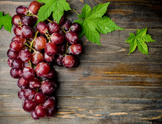 انگور قرمز و تخته چوبی