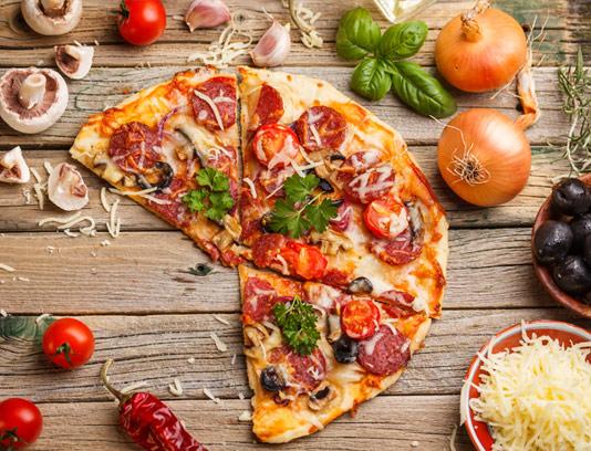عکس با کیفیت پیتزا روی میز چوبی