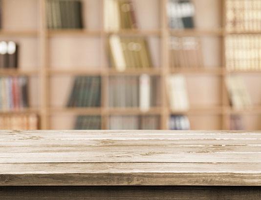 پس زمینه میز چوبی و کتابخانه